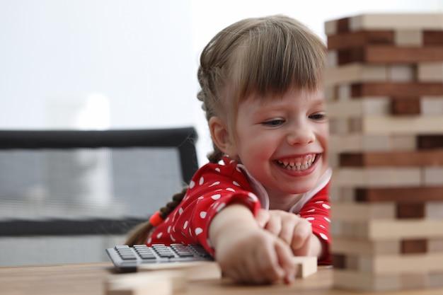 La bambina si siede a tavola e ride mentre gioca