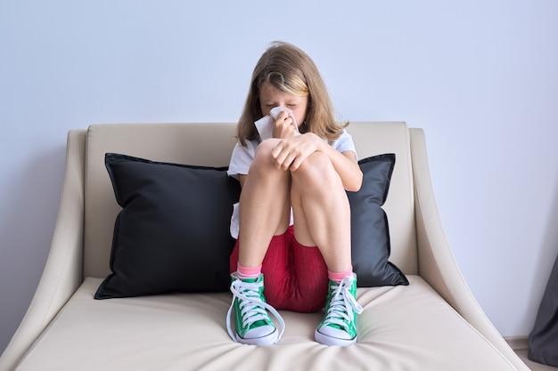 Bambina che starnutisce in un fazzoletto seduto a casa sul divano, stagione fredda