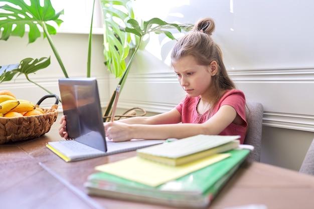Bambina che studia a casa utilizzando la tavoletta digitale. didattica a distanza, lezione online, videoconferenza, lezioni scolastiche in formato elettronico. scuola moderna, tecnologia, educazione, concetto di bambini.