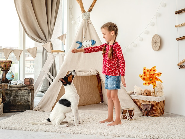 Ragazza bambino formazione fox terrier cane nella luce camera dei bambini