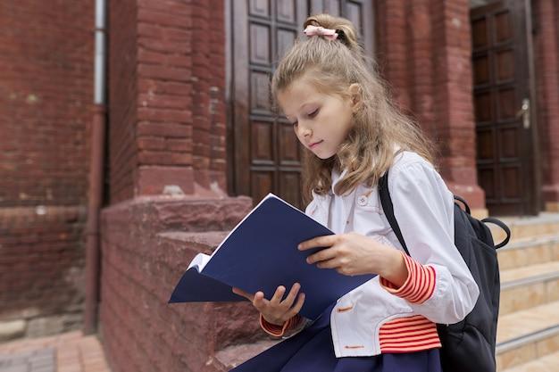 Bambina in uniforme con zaino seduto nel taccuino di lettura cortile della scuola, copia spazio. ritorno a scuola, inizio delle lezioni, educazione, conoscenza, lezioni, concetto di bambini