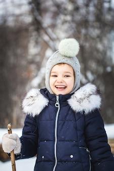 Bambina che cammina nella foresta invernale in una giacca blu e un cappello grigio