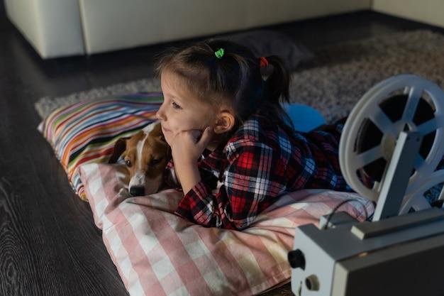 Bambina che guarda un vecchio film su un proiettore cinematografico vintage retrò con un cane