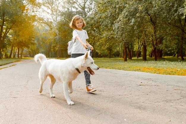 Bambina con un cane che cammina nel parco
