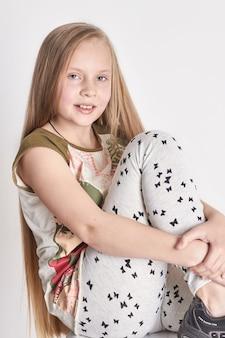 Bambina con lunghi capelli lussuosi, un bel sorriso. emozioni di gioia sul viso. ragazza in posa su sfondo chiaro. look estivo