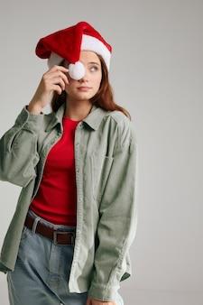 Ragazza con un cappello di natale con un pompon e una maglietta rossa giacca jeans modello capodanno