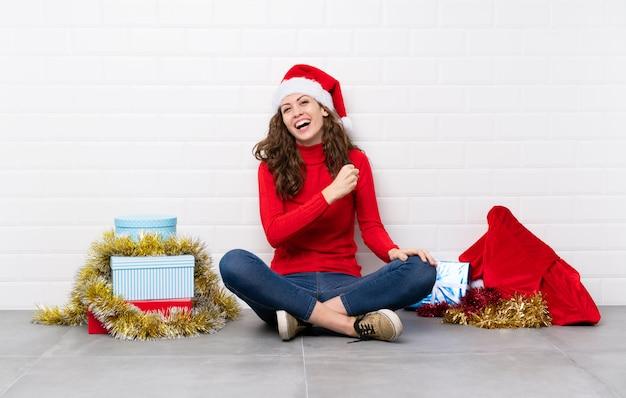 Ragazza nelle feste di natale che si siedono sul pavimento che celebra una vittoria