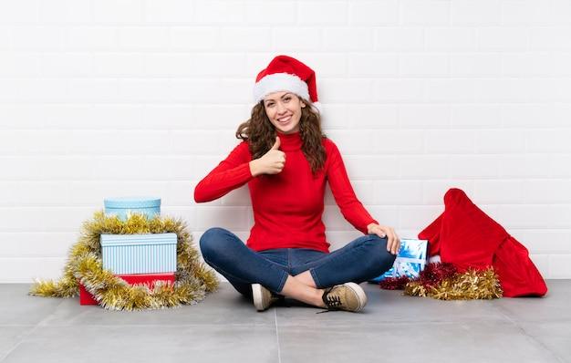 La ragazza nelle feste di natale che si siedono sul pavimento che dà un pollice aumenta il gesto