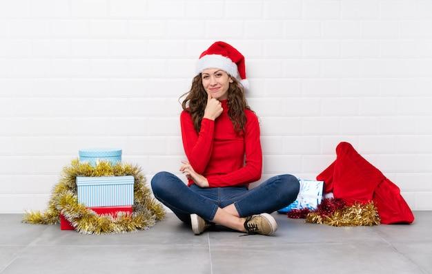 Ragazza nelle feste di natale che si siedono sulla risata del pavimento