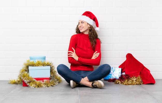 Ragazza nelle feste di natale che si siedono sul pavimento che osserva al lato
