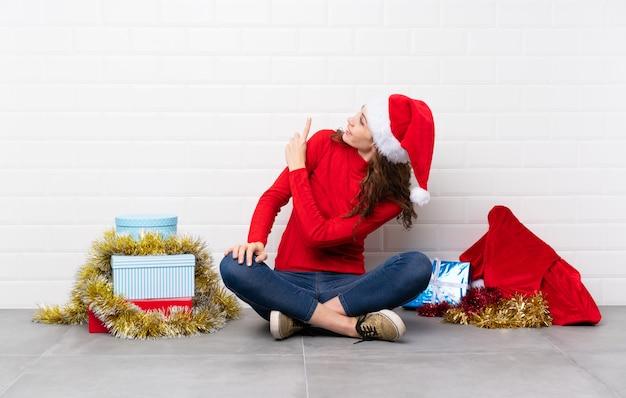 Ragazza nelle feste di natale che si siedono sul pavimento che indica indietro con il dito indice