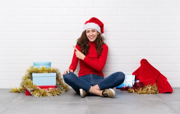 Ragazza nelle feste di natale che si siedono sul pavimento che indica barretta il lato