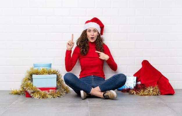 Ragazza nelle feste di natale che si siedono sul pavimento con espressione facciale di sorpresa