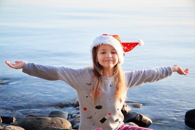 Una ragazza con un cappello rosso di natale si siede in riva al mare con le braccia tese. in viaggio per le vacanze invernali