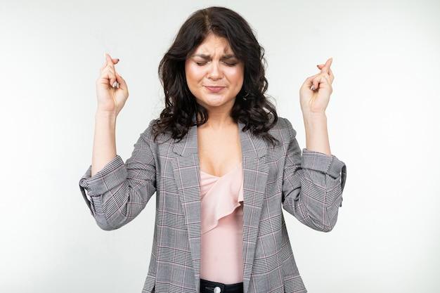 La ragazza in una giacca grigia a quadretti classica prega graffiare le dita su un bianco