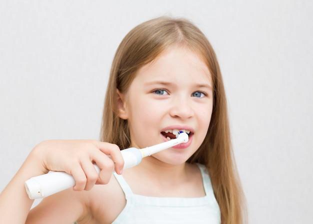 La ragazza si pulisce i denti con uno spazzolino elettrico. procedure igieniche mattutine. un bellissimo sorriso. denti bianchi. Foto Premium