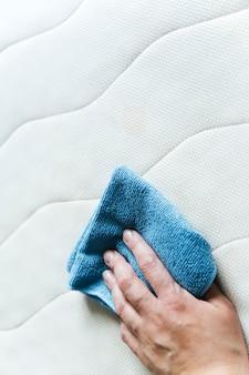 Una ragazza pulisce un materasso il concetto di una casa pulita