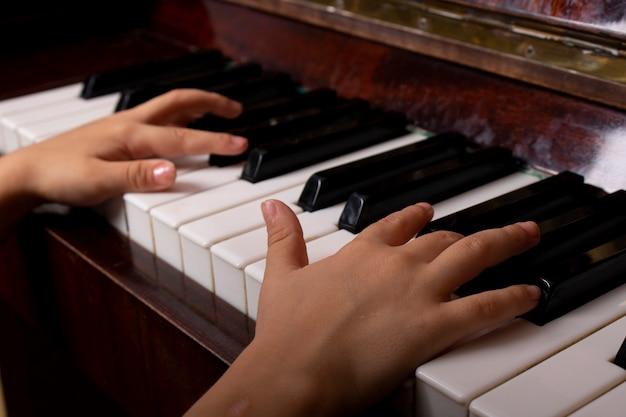 Una ragazza che ritaglia la tastiera del pianoforte da vicino