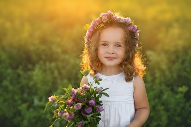 Ragazza in un campo di trifoglio al tramonto che tiene i fiori nelle sue mani.