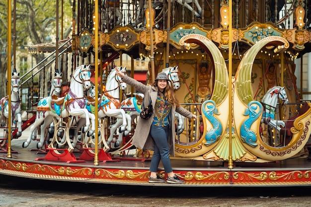 Una ragazza in un cappotto sulla giostra della città di avignone, in francia.