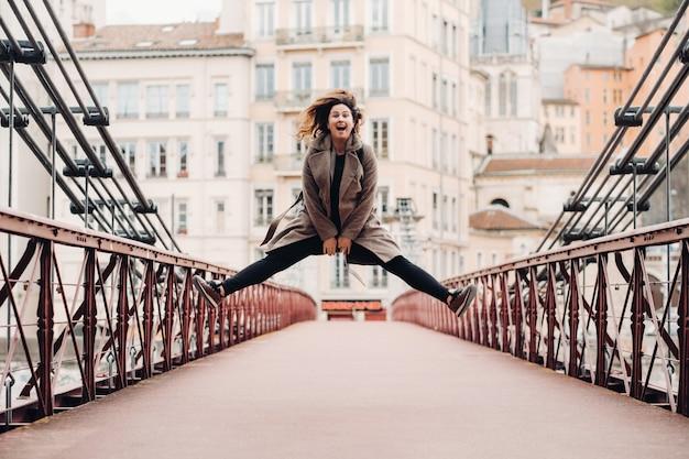 Una ragazza con un cappotto e i capelli sciolti salta emotivamente su un ponte nella città vecchia di lione. francia. ragazza con un cappotto in francia.