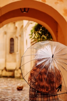 Ragazza in un cappotto con un ombrello trasparente dal retro