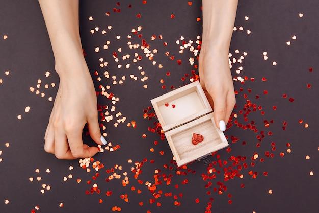 La ragazza raccoglie i cuori in una scatola per il giorno di san valentino. il 14 febbraio. un regalo a dnb per tutti gli innamorati