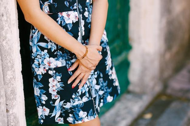 La ragazza in un vestito colorato con le mani giunte è appoggiata alla porta verde di un edificio in pietra