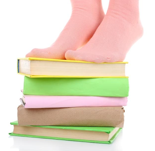 Ragazza in calzini colorati in piedi su una pila di libri su bianco