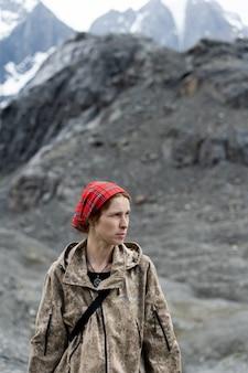Una ragazza in un comuffle sullo sfondo delle montagne. rainbow girl protegge la natura