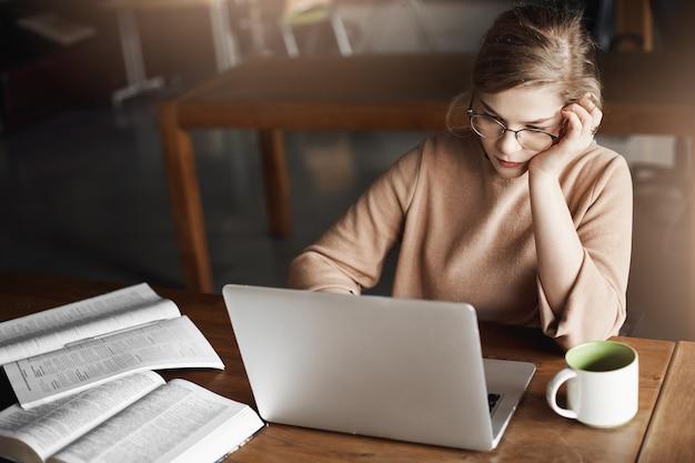 Ragazza che si concentra sul lavoro, corregge saggi, si appoggia la testa mentre è seduto al bar, lavora con il laptop, beve il tè per concentrarsi e prende appunti, controlla i dati nel conto aziendale