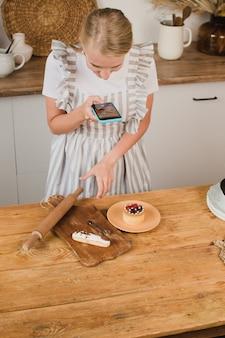Il pasticcere della ragazza fa una foto dei cupcakes su uno smartphone. concetto di blog