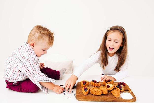 Pasticcere della ragazza che grida a suo fratello che disturba la sua cucina. i bambini preparano torte dolci, il ragazzino cerca di rubare bacche per roba
