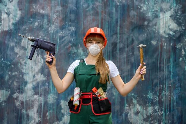 Ragazza in abiti da costruzione e dispositivi di protezione in posa con un trapano e un martello sul muro grigio.