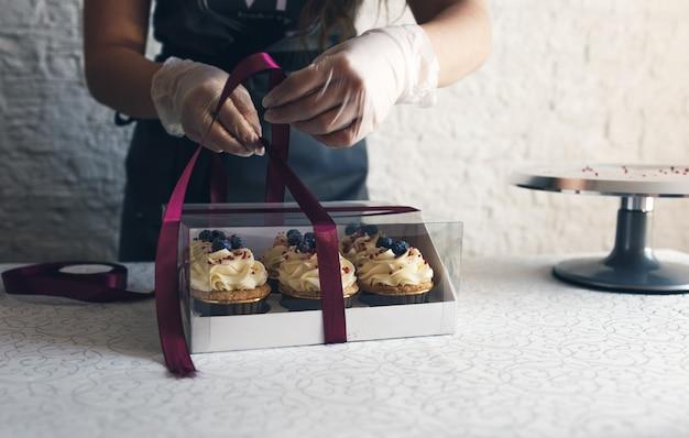 Una ragazza cuoca con un grembiule grigio confeziona cupcakes con crema in una confezione regalo per inviare l'ordine al cliente. cuocere a casa.