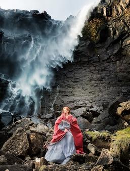 Una ragazza cosplayer con un mantello rosso rimane vicino alla cascata di fossa, streymoy, isole faroe