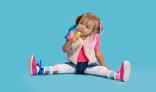 Una ragazza in costume e capelli colorati si siede sul pavimento e mangia chupachups. concetto di halloween e dolci.