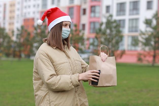 Il corriere della ragazza in maschera protettiva e cappello di babbo natale tiene un sacchetto di carta e una tazza di caffè