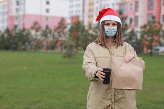 Il corriere della ragazza in maschera protettiva e cappello di babbo natale tiene il sacchetto di carta con i prodotti e la tazza di caffè