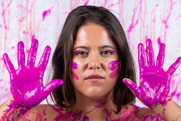 Ragazza ricoperta di vernice rosa che si diverte ed è libera, su un concetto che aiuta contro la consapevolezza del cancro al seno e la liberazione delle donne.