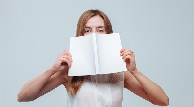 Ragazza che si copre il viso con un libro con la copertina bianca
