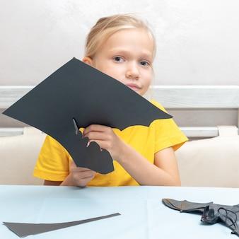 Una ragazza taglia una decorazione di halloween a casa da carta nera. decorazioni per la casa artigianali fai da te. il bambino fa mestieri di carta, origami