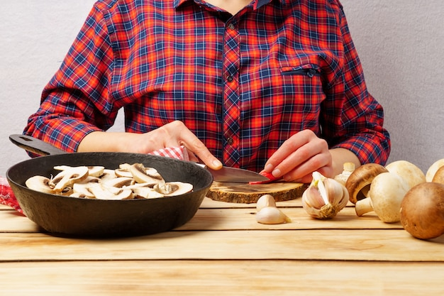 La ragazza taglia la paprika. una ragazza con una camicia a quadri rossa prepara i funghi. sfondo di legno