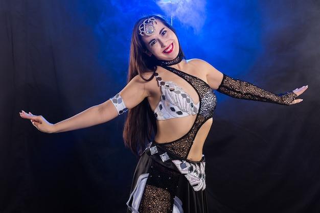 Ragazza che balla la danza del ventre, fusion o tribale. una donna in un bellissimo costume dimostra movimenti affascinanti e gentili nella danza.