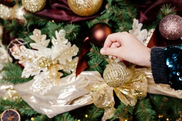 La ragazza decora un albero di natale. la bella ragazza passa la tenuta del giocattolo di natale dell'oro sul fondo dell'albero di natale. natale, decorazione, vacanze e concetto di persone