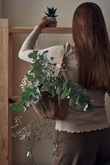 La ragazza decora uno scaffale in legno con una borsa ecologica con rami di eucalipto, fiori, piante d'appartamento