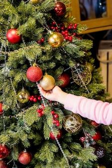 Ragazza che decora l'albero di natale appendendo ornamenti prima delle vacanze.bambino che decora la casa