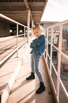 Ragazza in vestiti di jeans che balla hip-hop nel parcheggio dell'auto