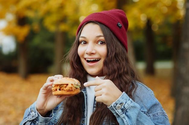 Una ragazza con una giacca di jeans e un cappello rosso con un hamburger in mano guarda la telecamera e sorride