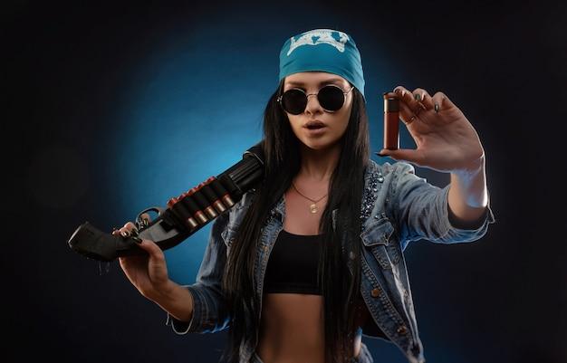 La ragazza con una giacca di jeans con un fucile da caccia